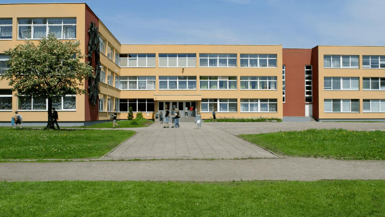 Établissement scolaire avec un arbre et une pelouse davant