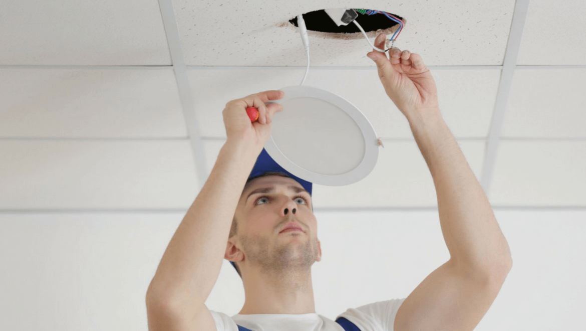 Electrician replacing a recessed