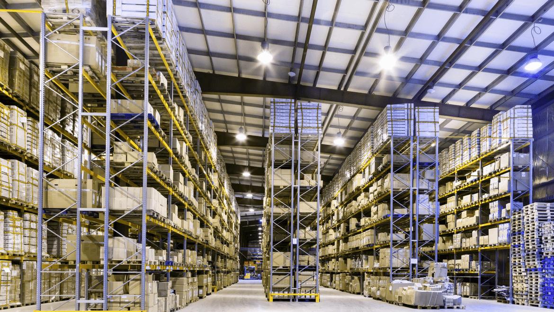 Entrepôt avec haut plafond et grandes étagères éclairé