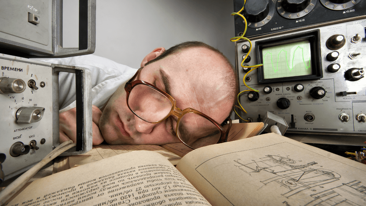 Man with glasses sleeping on his desk with lumen measurement tools