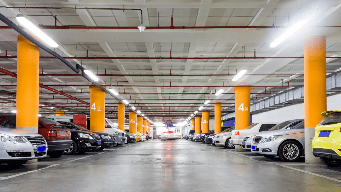 Indoor parking lot lit with cars and orange poles