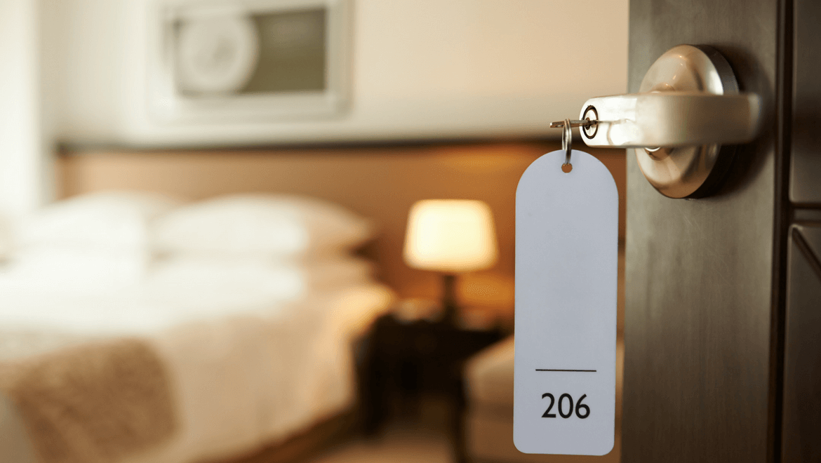 lighting in hotels: hotel room door with a key inside and bedside table lamp