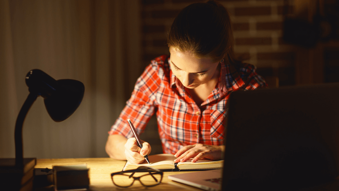 lighting and concentration: A woman with a red shirt at her desk writing with a desk light enlighting her project