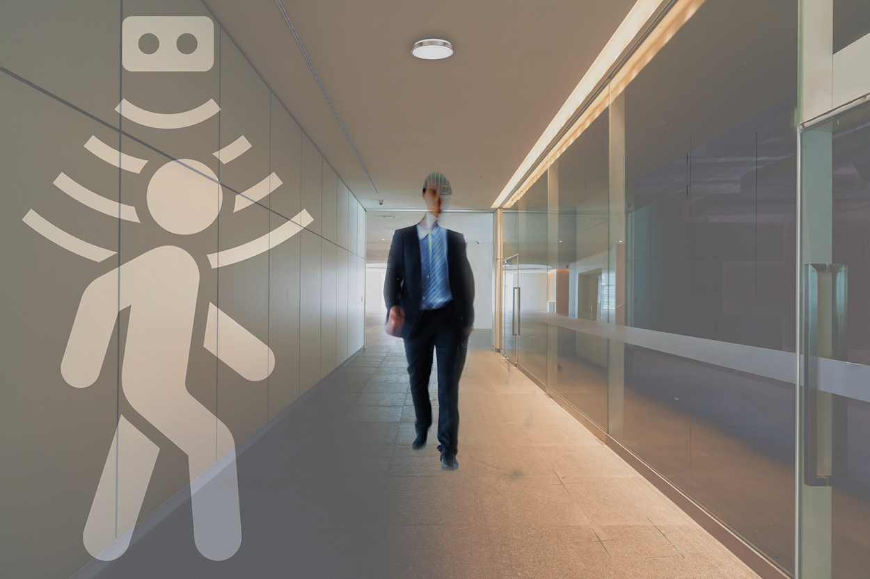 post-pandemic office lighting in a building corridor where a worker if walking and the motion sensor of the ceiling light get activated